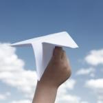 紙飛行機をとばす子どもの手